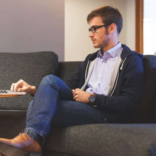 photo of a man on a laptop representing a 1-hour video online therapy call with Synergy eTherapy