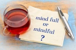 "Photo of a cup of tea, a pen and a napkin that says, ""mind full or mindful?"" Representing the benefits of online mindfulness training in Iowa."