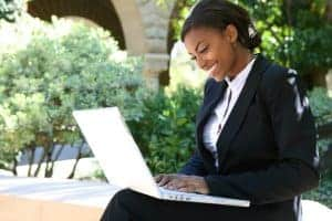 African American woman in a business suite with a computer she uses for online therapy in Minnesota.