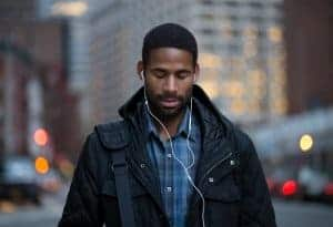 Young african american man walking with headphones in while zoning out | online therapy for anxiety | Synergy eTherapy