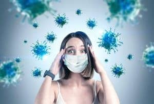 anxious woman is surrounded by germs. Get online anxiety treatment and online therapy with Synergy eTherapy